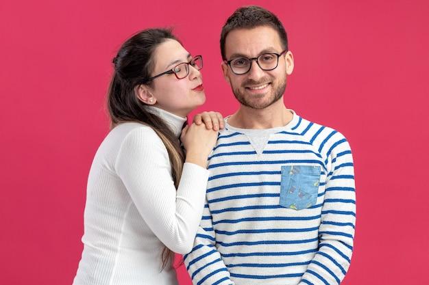 핑크 벽 위에 서있는 발렌타인 데이를 축하하는 그녀의 웃는 남자 친구를 키스하려고 캐주얼 옷 행복한 여자에 젊은 아름 다운 부부