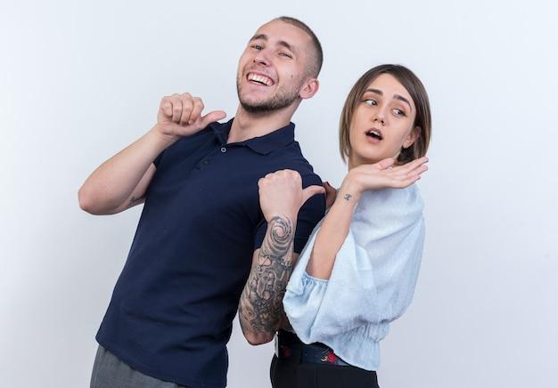 カジュアルな服装の男と女の幸せで陽気な男が白い壁の上に立って陽気な笑顔の彼のガール フレンドを親指で指し