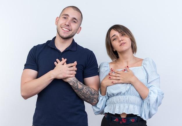 カジュアルな服装の男女が幸せでポジティブな、白い壁の上に立って感謝の気持ちを胸に手をつないでいる若い美しいカップル