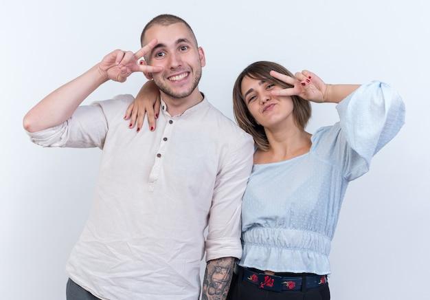 カジュアルな服装の男と女の若い美しいカップルが幸せで、白い壁の上に立っている v サインを示すポジティブ