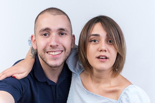 カジュアルな服装の男性と女性の幸せでポジティブな笑顔の若い美しいカップルが白い壁の上に陽気に立って