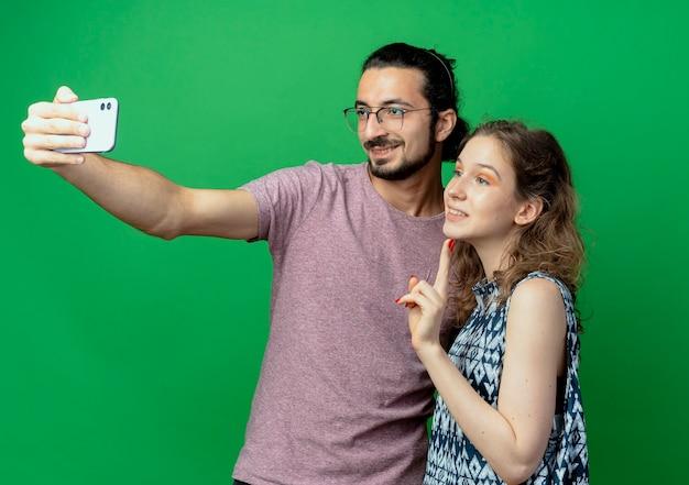 カジュアルな服装の若い美しいカップルの男性と女性、緑の壁の上に立っている彼のスマートフォンを使用してそれらの写真を撮る幸せな男