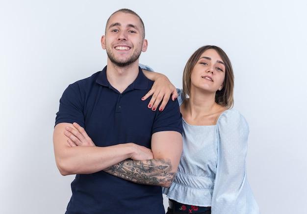 立っている陽気な笑顔を探しているカジュアルな服装の男女の若い美しいカップル