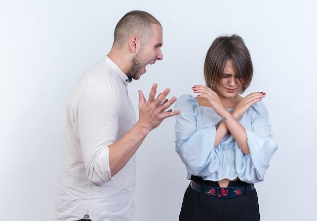 흰색 벽 위에 서있는 그의 혼란 여자 친구에 외치는 캐주얼 옷 남자와 여자 싸움 남자에서 젊은 아름 다운 부부