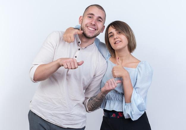 カジュアルな服装の男性と女性が白い壁の上に幸せで前向きな立ち姿を親指を現して陽気に笑っている若い美しいカップル