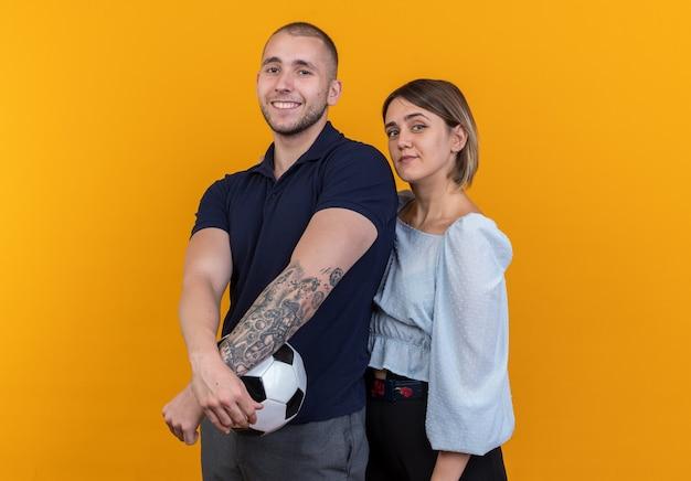 Молодая красивая пара в повседневной одежде мужчина с футбольным мячом и женщина, выглядящая счастливой и позитивной, весело улыбаясь, стоя