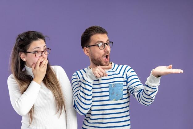 カジュアルな服を着た若い美しいカップルは、紫色の背景の上に立っているバレンタインデーを脇に見て驚いた男と女