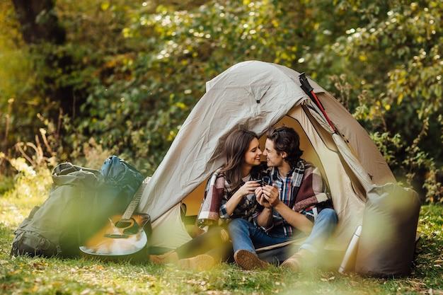 Молодая красивая пара в повседневном платье сидит в кемпинге возле палатки