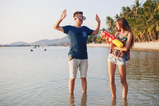 Молодая красивая влюбленная пара, играющая на тропическом пляже, летние каникулы, медовая луна, романтика, закат, счастливый, веселье, водяной пистолет, борьба, мужчина сдается, позитив, смешно