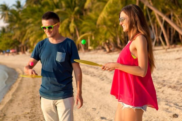 熱帯のビーチでピンポンをするのが大好きな若い美しいカップル、楽しんで、夏休み、アクティブ、笑顔、面白い、ポジティブ