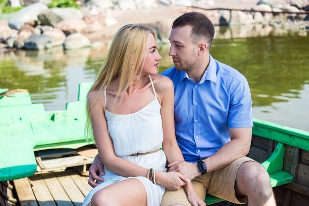 Молодая красивая пара в любви, сидя в старой лодке