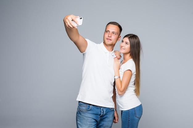 灰色の背景に分離された流行の服を着て幸せな笑顔の携帯電話と一緒にロマンチックな自画像の自撮り写真を撮るのが大好きな若い美しいカップル