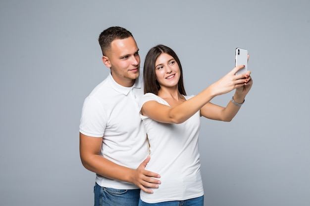 Молодая красивая пара в любви, делающая романтическое автопортретное селфи фото вместе с мобильным телефоном, улыбаясь счастливым в модной одежде, изолированной на сером фоне