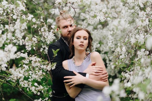 桜を背景に庭にいる若い美しいカップル1