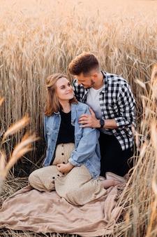 아름 다운 젊은 부부는 자연 속에서 쉬고 임신에 행복합니다. 가족과 임신. 사랑과 부드러움. 행복과 평온. 새로운 삶을 돌봅니다.