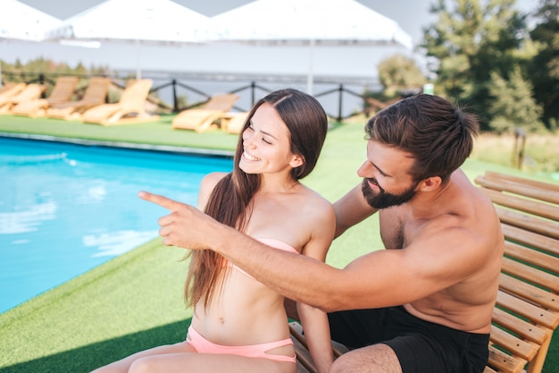 Young and beautiful couple is sitting on sunbeds and look to the left. giu is pointing with finger. girl smiles. they look happy.