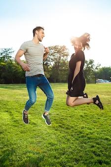 공원에서 점프 젊은 아름 다운 부부.
