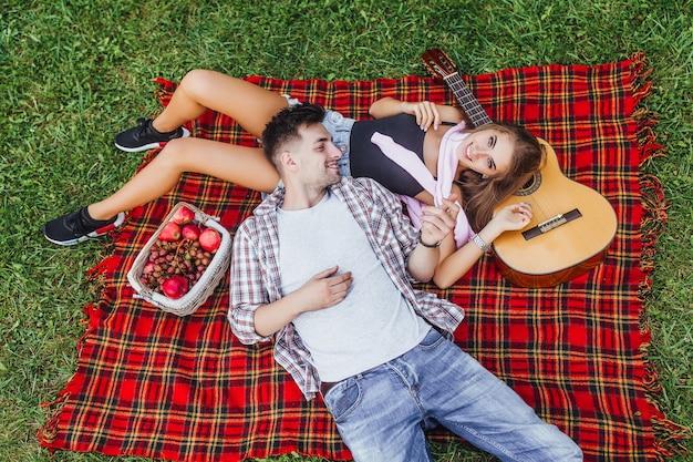 Молодая красивая пара лежит на одеяле ковра и смотрит друг на друга в одеяле ковра, а девушка смотрит в камеру.