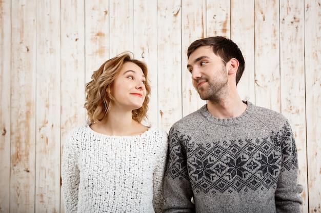 Молодая красивая пара, глядя друг на друга через деревянную стену