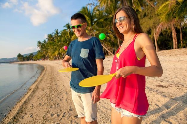 Giovane bella coppia innamorata giocando a ping pong sulla spiaggia tropicale, divertendosi, vacanze estive, attivo, sorridente, divertente, positivo