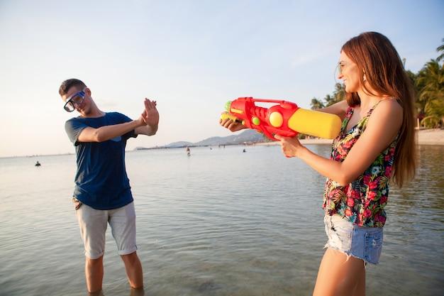 Giovane bella coppia innamorata che gioca sulla spiaggia tropicale, vacanze estive, luna di miele, romanticismo, tramonto, felice, divertirsi, pistola ad acqua, lotta, l'uomo si arrende, positivo, divertente