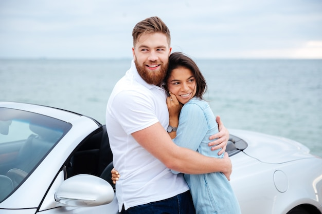Young beautiful couple in love standing at car at the seaside