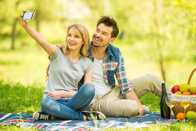 Young beautiful couple make selfie in forest.