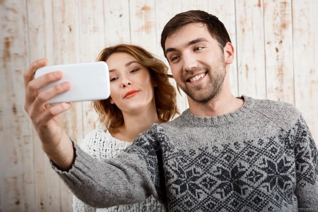 Молодая красивая пара делает селфи, улыбаясь на деревянной стене