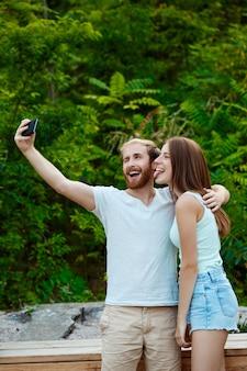 Giovani belle coppie che fanno selfie, sorridendo, camminando nel parco