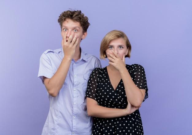 若い美しいカップルの男性と女性は混乱し、青い壁の上に立っている手で口を覆うことを心配しました