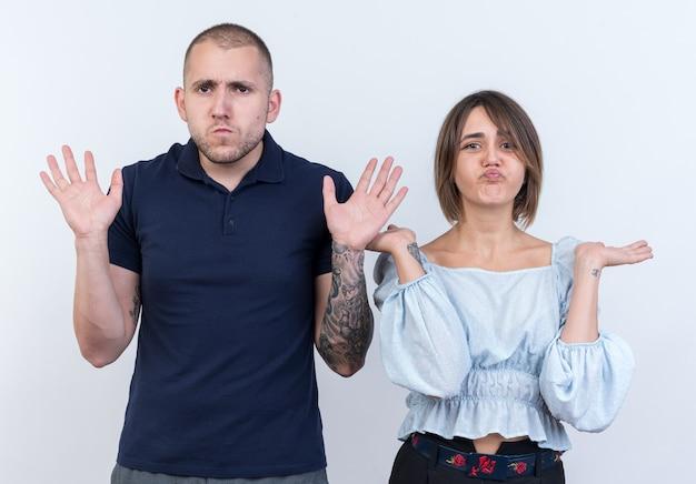 Молодая красивая пара мужчина и женщина смущены, разводя руками в стороны, не имея ответа, стоя над белой стеной