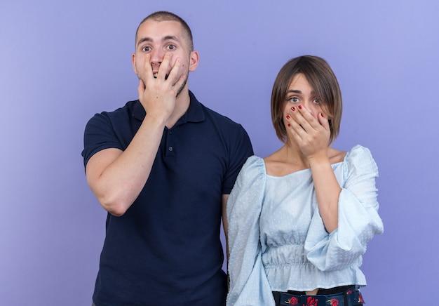 젊은 아름 다운 부부 남자와 여자 손으로 입을 덮고 파란색 벽 위에 서 충격을 받고