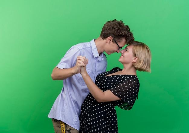緑の壁の上で幸せで楽しい一緒に踊る若い美しいカップルの男性と女性