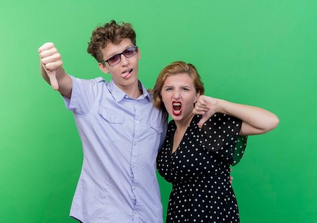 젊은 아름 다운 부부 남자와 여자는 녹색 벽 위에 서 아래로 엄지 손가락을 보여주는 불쾌