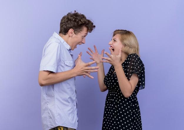 青い壁の上に立ってお互いを見て幸せで興奮している若い美しいカップルの男性と女性