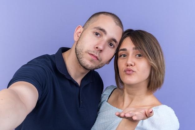 青い壁の上に立っている彼女の顔の前に手でキスを吹く若い美しいカップルの男と女の幸せとポジティブ