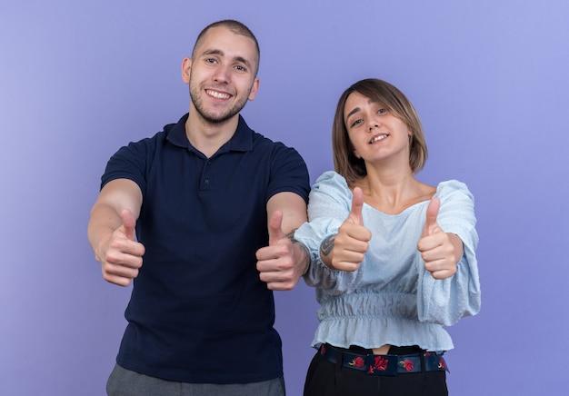 若い美しいカップルの男と女の幸せで肯定的な笑顔は、青い壁の上に立って親指を陽気に表示