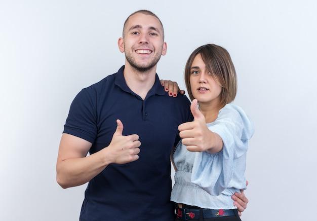 若い美しいカップルの男と女の幸せでポジティブな笑顔が白い壁の上に立って親指を陽気に現して
