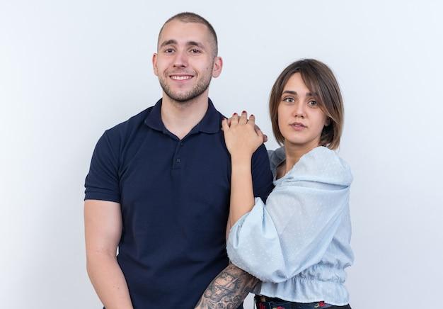 若い美しいカップルの男と女の幸せで肯定的な笑顔の女性が白い壁の上に立っている彼女のボーイ フレンドの肩に手をつないで