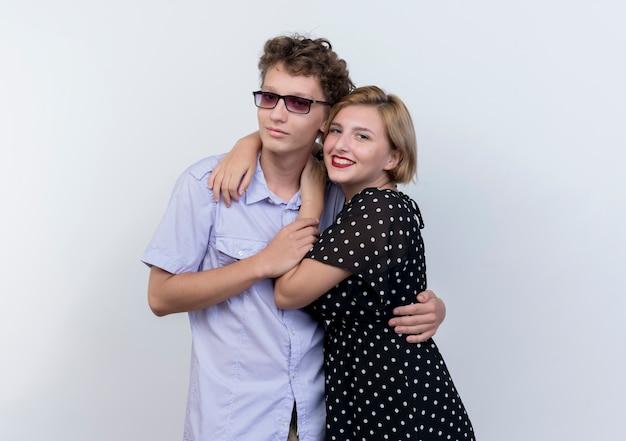 Молодая красивая пара мужчина и женщина счастливы в любви, обниматься, стоя над белой стеной