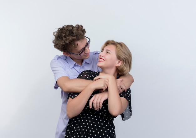 흰색 벽 위에 서 포옹 사랑에 행복 젊은 아름 다운 부부 남자와 여자