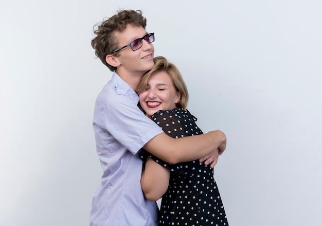 Молодая красивая пара мужчина и женщина счастливы в любви мужчина обнимает свою подругу, стоящую над белой стеной