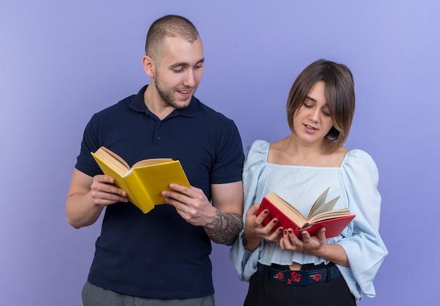 젊은 아름 다운 부부 남자와여자가 손에 책을 들고 행복 하 고 긍정적 인 유쾌 하 게 서 웃 고