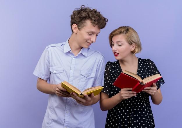 젊은 아름 다운 부부 남자와여자가 파란색 벽 위에 서 관심으로 그것을보고 책을 들고