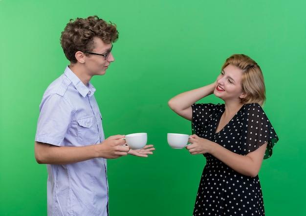 若い美しいカップルの男性と女性が緑の壁に幸せで前向きな笑顔で向かい合って立っているコーヒーカップを保持します。