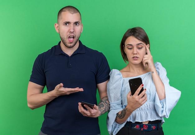 Молодая красивая пара мужчина и женщина, держащая смартфоны, выглядят смущенными и недовольными стоя