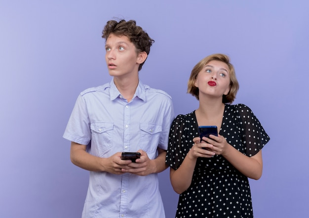 젊은 아름 다운 부부 남자와여자가 파란색 벽에 의아해 서 찾고 스마트 폰을 들고