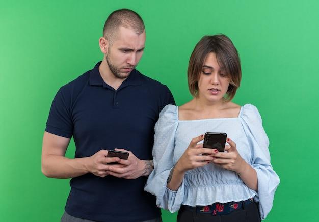 Молодая красивая пара мужчина и женщина, держащая смартфоны, мужчина с подозрением смотрит на смартфон стоя своей подруги