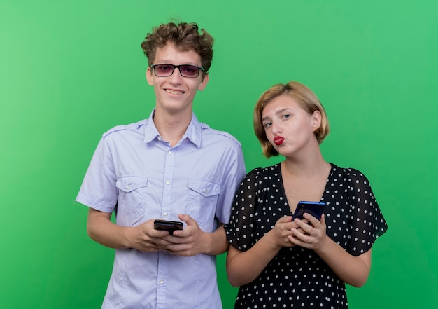 젊은 아름 다운 부부 남자와여자가 녹색 벽 위에 서 웃 고 스마트 폰 들고