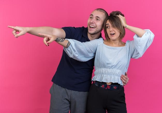 젊은 아름 다운 부부 남자와 여자는 분홍색 벽 위에 서있는 측면에 검지 손가락으로 제쳐두고 행복하고 정서적으로 가리키는 찾고